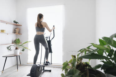Woman performing workout on elliptical trainer at home - AHSF02524