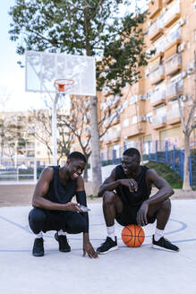 Basketball players using smartphone on basketball court - EGAF00016