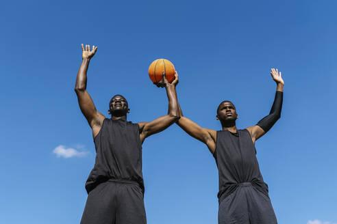Basektball player with raised arms and ball - EGAF00025