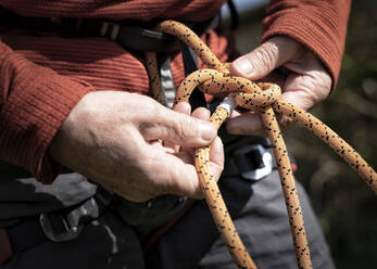 Tying a figure of eight to a rock climbing harness - ALRF01746