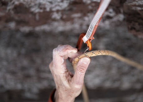 Clipping a climbing rope into a karabiner - ALRF01755