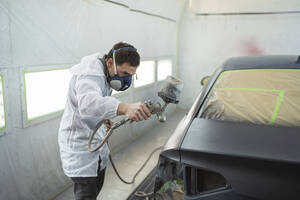 Body painter painting car in paint booth - SNF00020