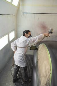 Body painter painting car in paint booth - SNF00023