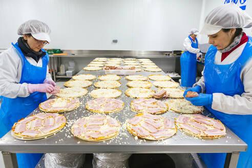Woman preparing pizzas in pizza company - XLGF00136