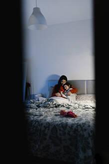 Mother and her little daughter cuddling together on bed - EGAF00048