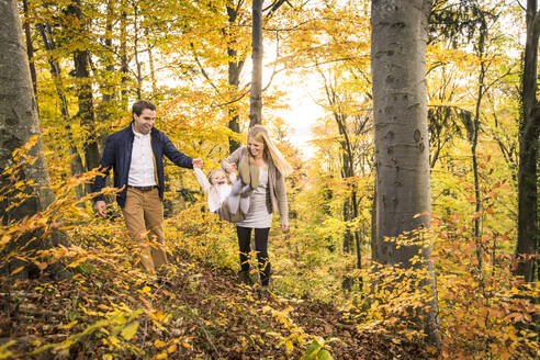 Happy mid adult parents swinging daughter while exploring forest during autumn - WFF00399