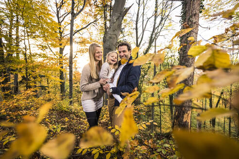Smiling parents and daughter exploring forest during autumn - WFF00405
