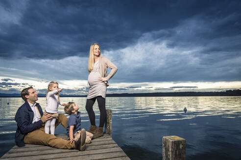 Full length of happy family on jetty at Starnberger See against cloudy sky - WFF00408