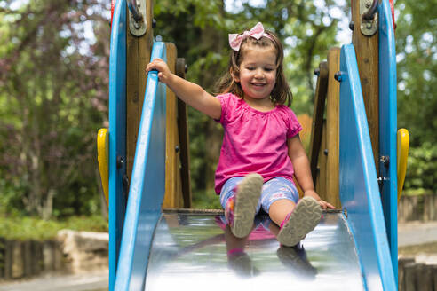 Portrait of smiling little girl on playground slide - MGIF00933