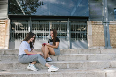 Full length of smiling young female students talking while sitting on steps at campus in university - GRCF00185