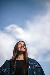 Low angle view of happy young woman standing against sky - GRCF00191