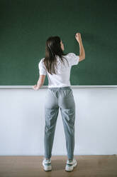 Full length rear view of young female student writing on blackboard in university classroom - GRCF00194