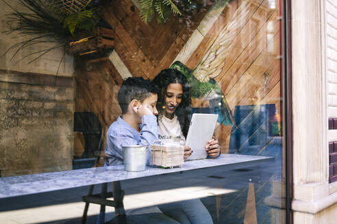 Smiling woman sitting with son while using digital tablet in restaurant seen from window - DGOF00940
