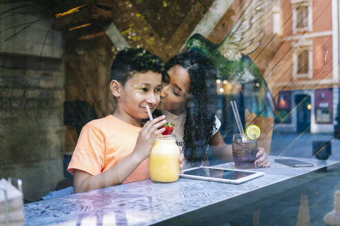 Young woman kissing son drinking smoothie seen through restaurant window - DGOF00943