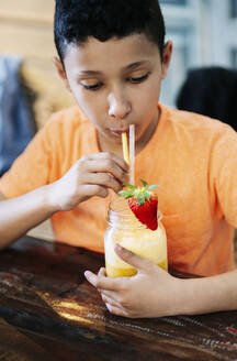 Boy drinking smoothie from straw while sitting at table in restaurant - DGOF00952