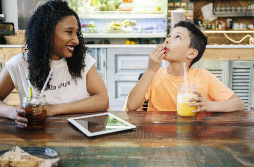 Smiling young woman looking at son eating strawberry in restaurant - DGOF00958