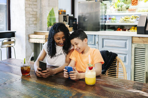 Cheerful mother and son using mobile phones at table in restaurant - DGOF00961