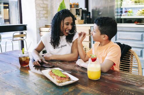 Boy feeding happy mother with fork while sitting at restaurant - DGOF00964