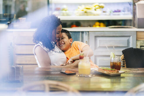 Young woman enjoying while embracing son at restaurant - DGOF00970