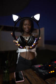 DJane showing her headphones with shining cat ears - VEGF02125