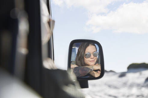 Smiling young woman wearing sunglasses in side-view mirror of car - CAIF27243
