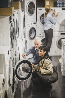 High angle view of mature owner pointing to washing machine while female customer crouching in electronics store - MASF18112