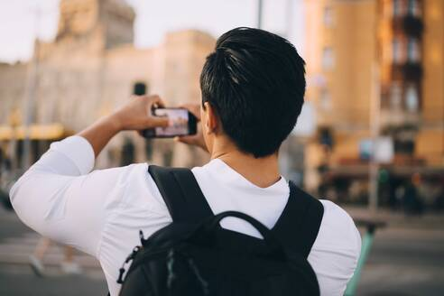 Rear view of young man photographing through mobile phone in city - MASF18142