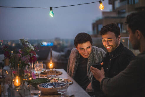 Man showing smart phone to smiling male friends while sitting on terrace during social gathering - MASF18208