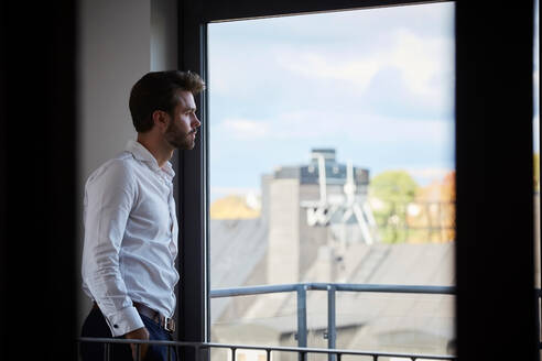 Contemplating businessman looking through window while standing by office window - MASF18274