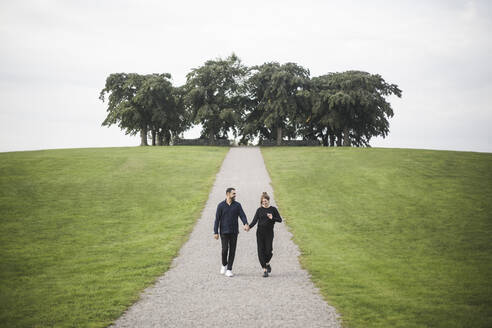 Smiling couple walking amidst grassy field against trees and sky - MASF18379