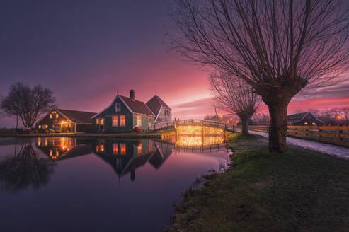 Netherlands, North Holland, Zaanse Schans, Riverside town houses at purple moody dawn - DVGF00088