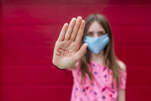 Girl with face mask showing palm of her hand, saying stop - SARF04559