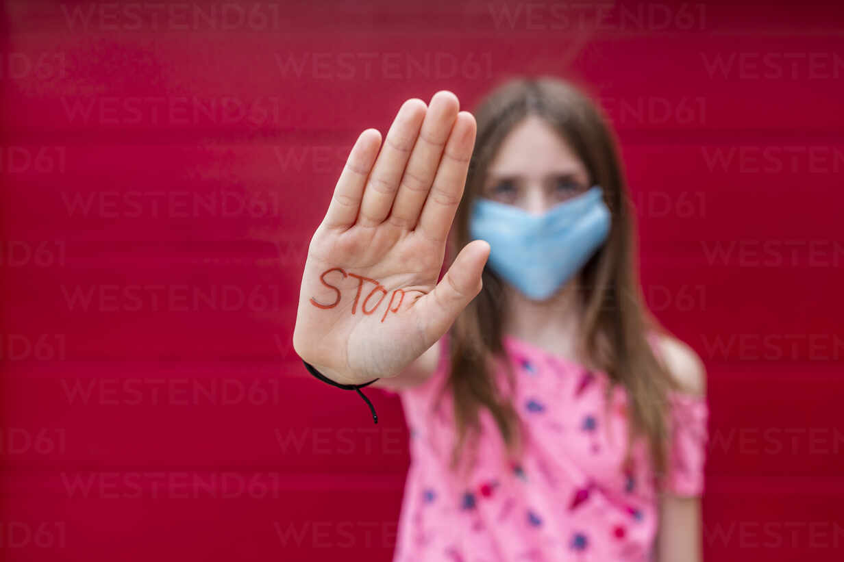 Girl with face mask showing palm of her hand, saying stop - SARF04559 - Sandra Roesch/Westend61