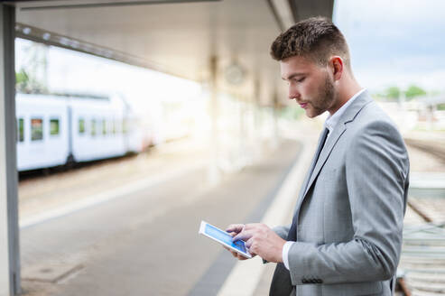 Young businessman using tablet at the train station - DIGF10444