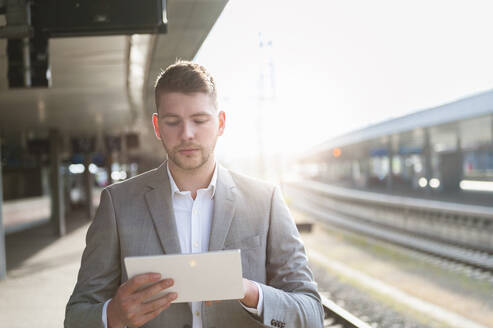 Young businessman using tablet at the train station - DIGF10447