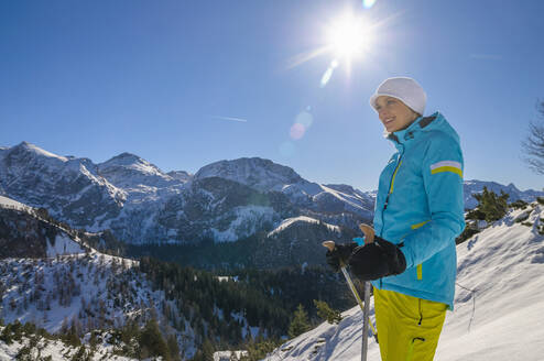 Smiling beautiful woman hiking on snow while looking away against blue sky - DIGF10456