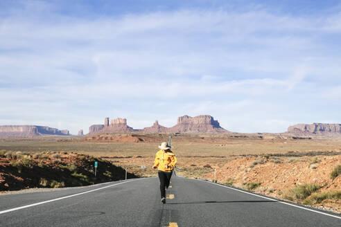 Full length of woman running on desert road against sky, Monument Valley Tribal Park, Utah, USA - DGOF00983