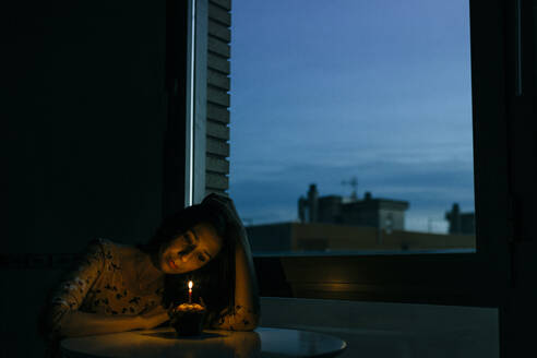 Lonely birthday woman looking at burning candle on cupcake by window in room during sunset - GMLF00183