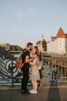 Affectionate young couple on a bridge in the city, Berlin, Germany - VBF00004