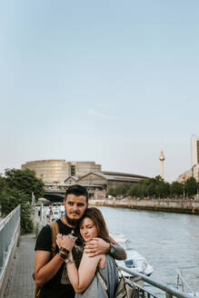 Young couple hugging at River Spree, Berlin, Germany - VBF00016