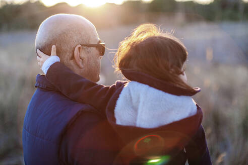 Rear view of mature man with granddaughter at countryside during sunset - EGAF00060