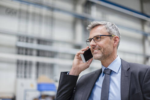 Smiling businessman on the phone in a factory - DIGF10559