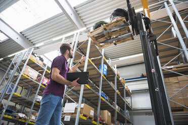 Warehouseman and goods on forklift in high rack warehouse - DIGF10601
