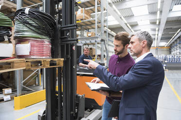 Two men and worker on forklift in high rack warehouse - DIGF10604