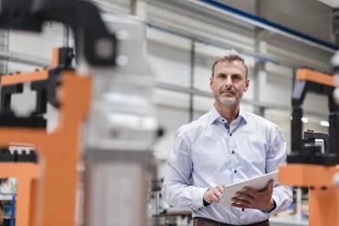 Portrait of mature man using tablet on factory shop floor - DIGF10616