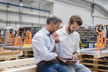 Two men sharing tablet on factory shop floor - DIGF10619