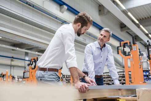 Two men talking on factory shop floor - DIGF10625