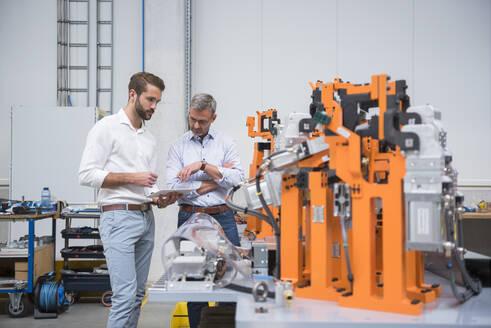 Two men sharing tablet on factory shop floor - DIGF10628