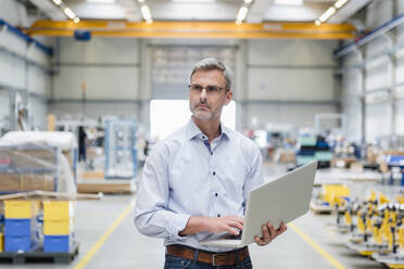 Mature man holding laptop on factory shop floor - DIGF10634