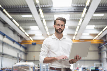 Young man holding laptop on factory shop floor - DIGF10637
